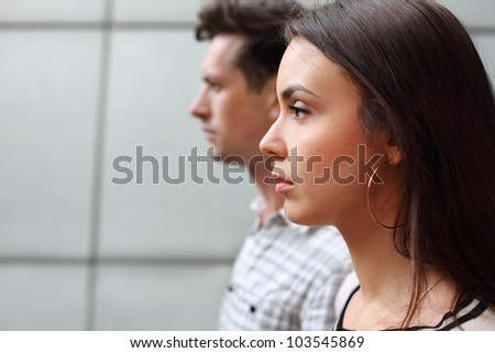 Pensive man and woman stand near gray wall and look away; facial profile; focus on woman - stock photo