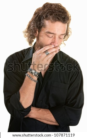 Pensive man covering his mouth while looking down - stock photo