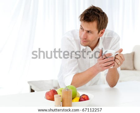 Pensive man drinking coffee standing at a table in the living room - stock photo