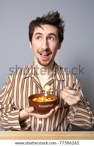 Pensive man in pyjamas at the table - stock photo