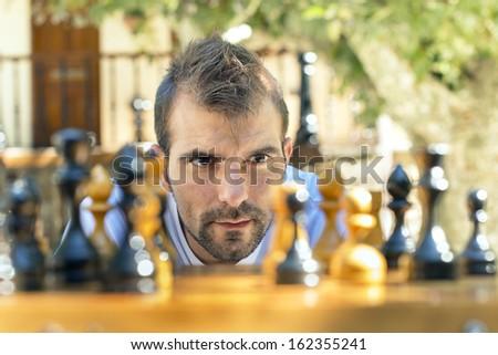 Pensive man play chess. - stock photo