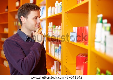 Pensive man shopping for products in a drugstore - stock photo