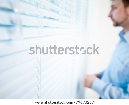 Pensive man thinking of something behind venetian blind - stock photo