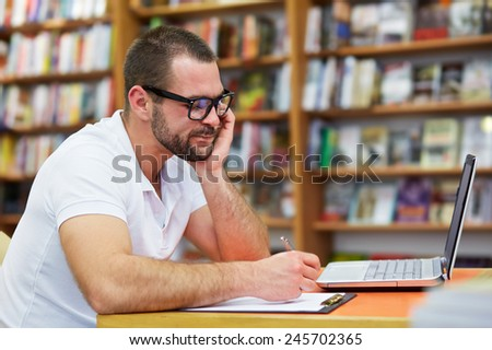 Pensive man working with a laptop in the library - stock photo