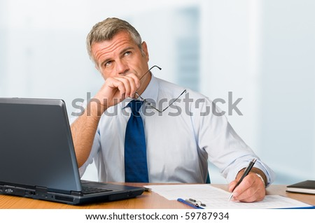Pensive mature businessman looking up with concentration and writing in his paperwork at office - stock photo