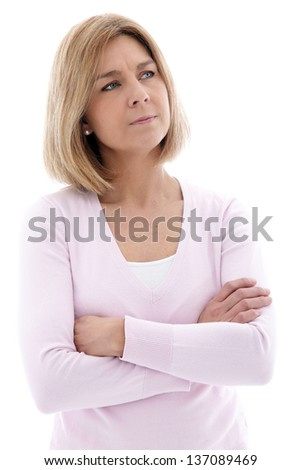 Pensive middle aged blond woman standing with folded arms staring up into the air with a frown, isolated on white - stock photo