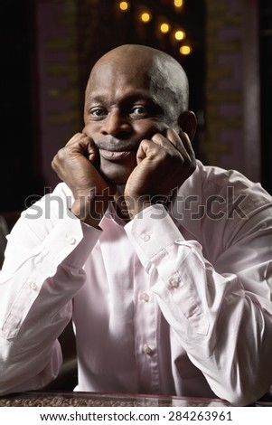 Pensive middle-aged guy in a pink shirt sitting at the table leaning on fists - stock photo