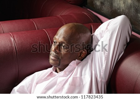 Pensive middle-aged guy laying down on sofa closeup - stock photo