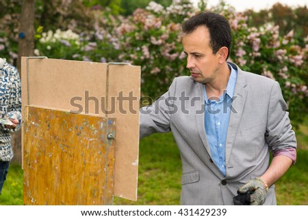 Pensive middle-aged male  artist standing in front of his sketchbook painting pictures with  oils and acrylics paint during an art class in a garden - stock photo