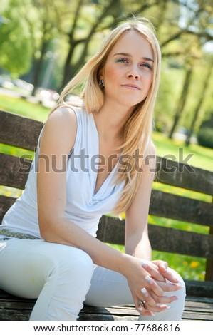Pensive mood - woman on bench - stock photo