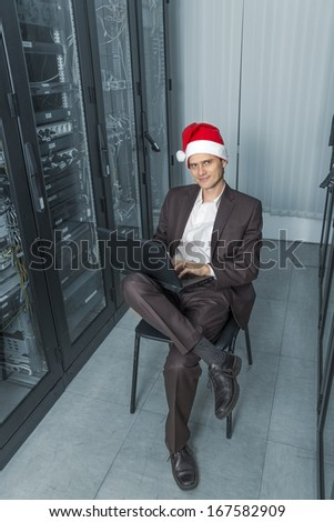 pensive network Engineer  in the server in Santa Claus sitting on a chair with gadget  on colorize background