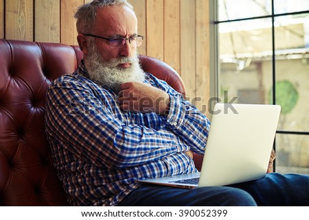 pensive old man sitting on couch and looking at laptop - stock photo
