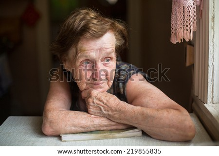 Pensive old woman with a book near window in the room of his house. - stock photo