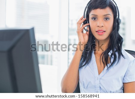 Pensive operator looking at camera in office - stock photo