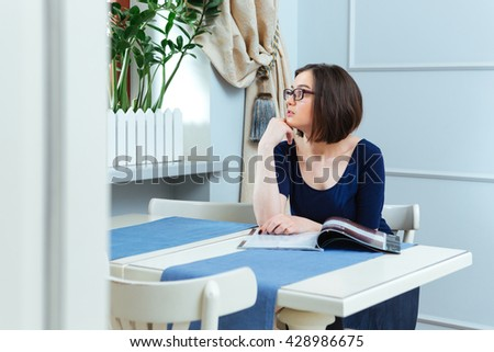 Pensive pretty young woman reading magazing and thinking in cafe - stock photo