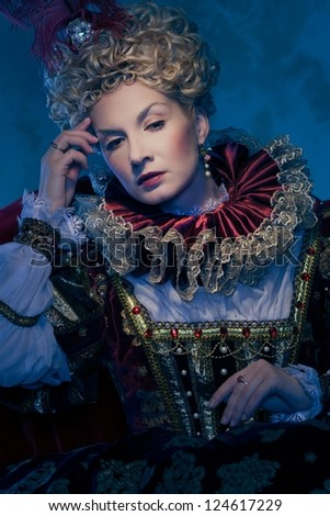 Pensive queen in royal dress - stock photo