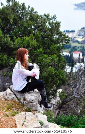 pensive redheaded girl sitting  on the cliff