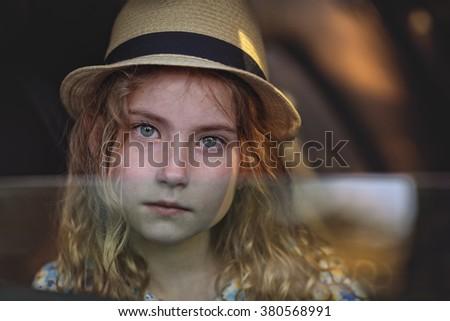 Pensive sad girl in the car - stock photo