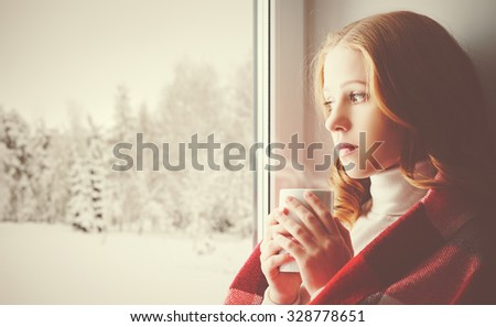 Pensive sad girl with a warming drink looking out the window in the winter forest - stock photo