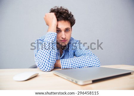 Pensive sad man sitting at the table with laptop over gray background - stock photo