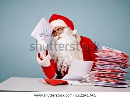Pensive Santa Claus with Christmas letter sitting by table - stock photo