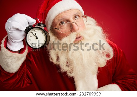 Pensive Santa with alarm clock showing five minutes to xmas by his ear - stock photo