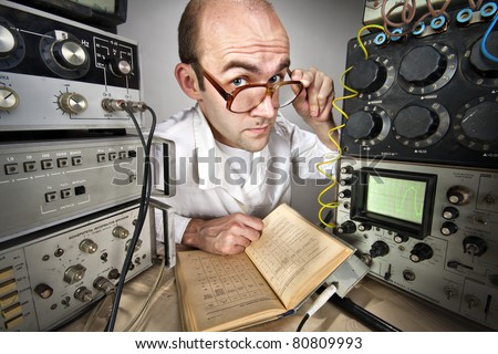 Pensive scientist reading book at vintage technological laboratory - stock photo