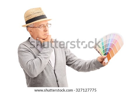 Pensive senior gentleman looking at a color swatch and choosing a color isolated on white background