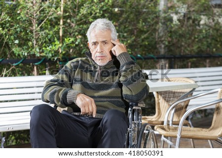 Pensive Senior Male Patient Sitting In Wheelchair At Lawn - stock photo