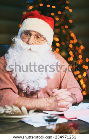 Pensive senior man in Santa cap and beard - stock photo