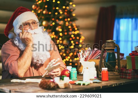 Pensive senior man in Santa cap and beard painting wooden deers - stock photo