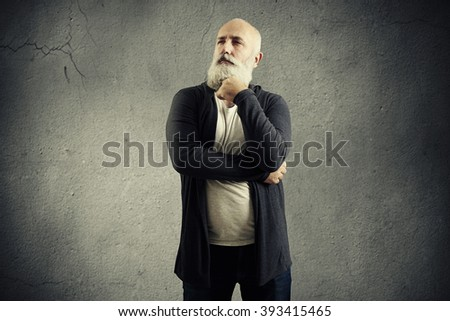 pensive senior man looking into the distance over dark background - stock photo
