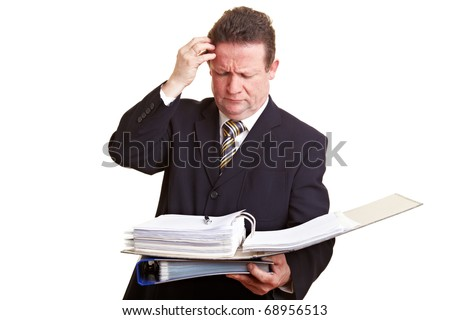 Pensive senior manager scratching his head and looking at files - stock photo