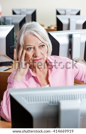 Pensive Senior Woman Sitting At Computer Desk In Classroom - stock photo