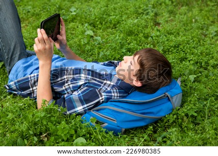 pensive, serious teenager lying on grass in park with tablet, outdoor, schoolboy - stock photo