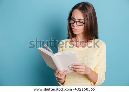 Pensive smart young girl reading book isolated on the blue background - stock photo
