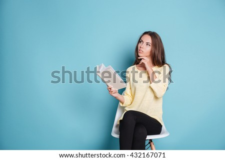 Pensive smart young girl thinking about something isolated on the blue background - stock photo