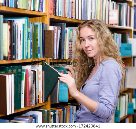 Pensive student in the library surrounded by books - stock photo