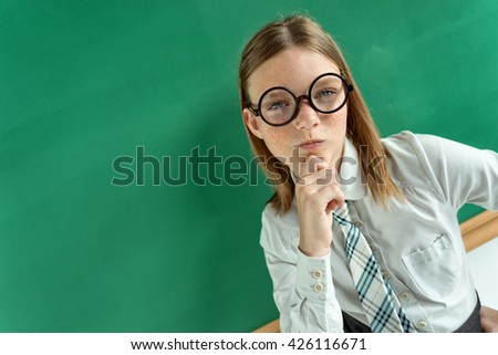 Pensive student thinking and looking towards near blackboard. Photo of young students in classroom, education concept - stock photo