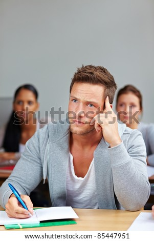 Pensive student thinking and taking notes in university class - stock photo
