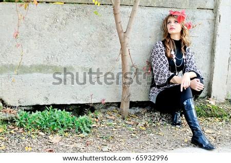 pensive teen girl sitting alone  near the wall - stock photo