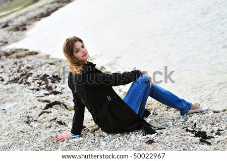pensive  teen girl sitting on the pebble close to sea in spring time