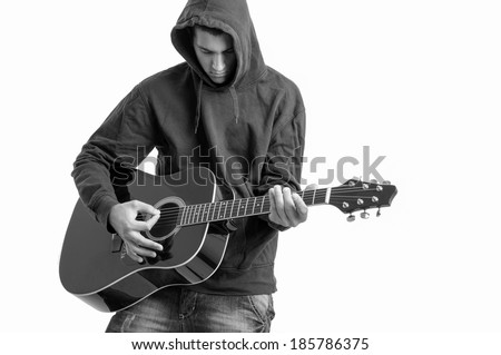 Pensive Teenager dressed in a hoodie, writing a song about life at acoustic guitar - stock photo