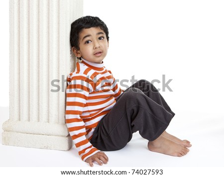 Pensive Toddler Sitting Against a Column - stock photo
