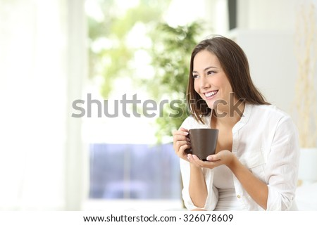 Pensive woman drinking coffee or tea and thinking looking sideways at home - stock photo