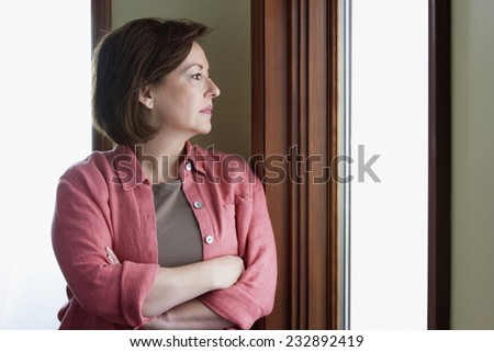 Pensive Woman Gazing Out Window - stock photo