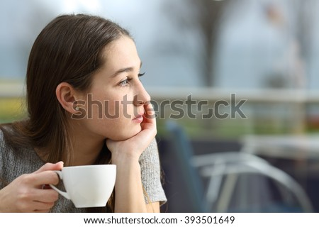 Pensive woman holding a coffee cup looking away in a restaurant terrace in a rainy day - stock photo