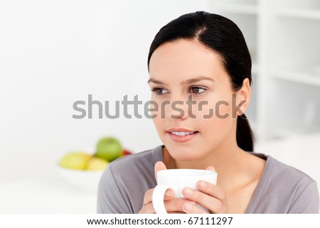 Pensive woman holding a cup of coffee sitting in the kitchen at home - stock photo