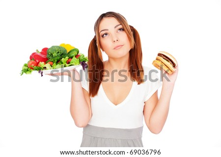 pensive woman holding fresh vegetable and burger