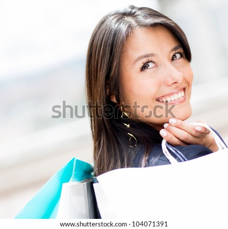 Pensive woman holding shopping bags and smiling - stock photo